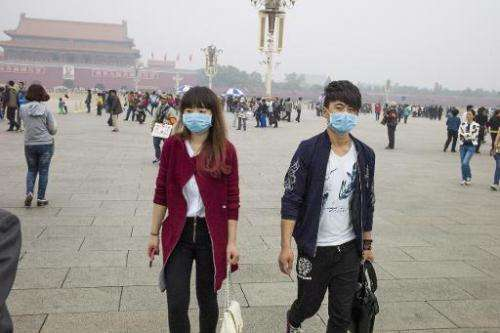 A couple walk with a face mask on Tiananmen Square in Beijing on October 11, 2014