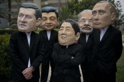 Activist depicting the PM's of Canada, Stephen Harper (L), India, Narendra Modi (2-R) and Japan, Shinzo Abe (C) and presidents o
