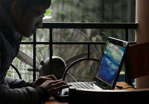 A customer is seen using a laptop at a coffee shop in Hanoi, Vietnam, on November 28, 2013