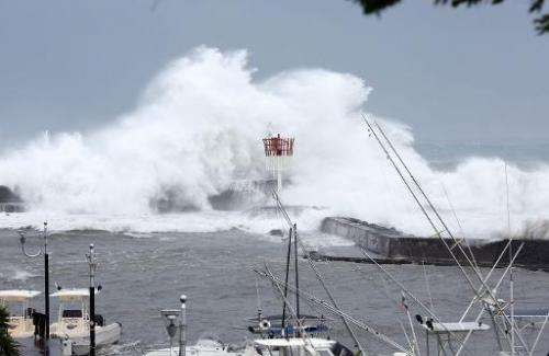 A cyclonic swell sweeps a pier on January 2, 2014 in Saint-Gilles, in the French La Reunion overseas island