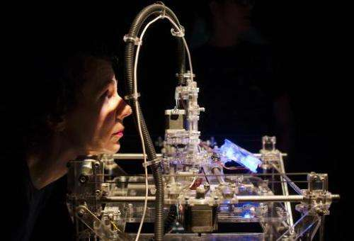 A designer looks at a 3D printer during an exhibition in London on April 23, 2013