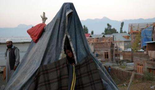 A displaced woman sits in a makeshift tent in Srinagar on September 16, 2014 following heavy floods