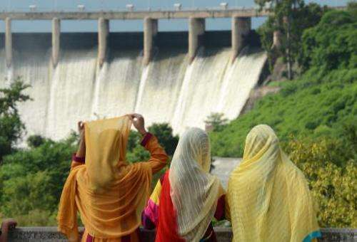 A family looks at the Rawal dam spill way during the Eid holidays in Islamabad on August 10, 2013
