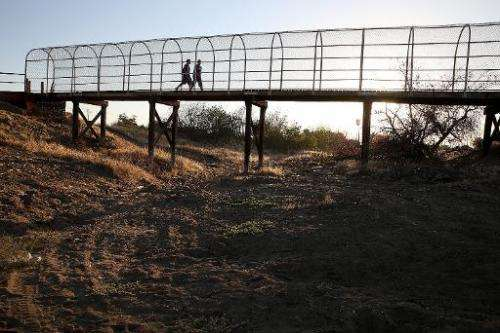 A footbridge spans a completely dry river bed, in Porterville, California, on September 4, 2014