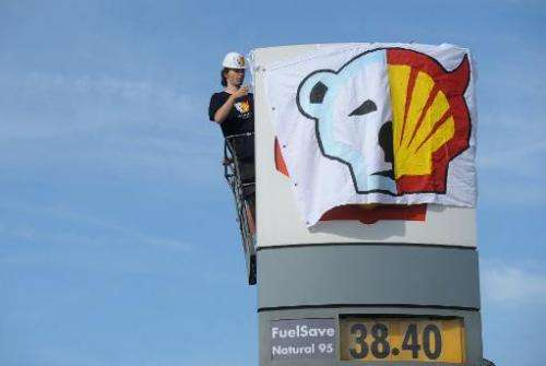 A Greenpeace activist half covers the Shell logo at a petrol station in Prague on May 10, 2012