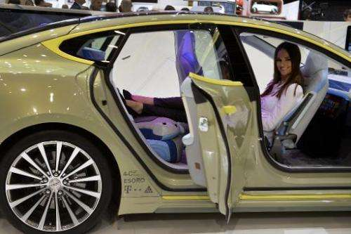 "A hostess poses inside the new Rinspeed ""XchangE"" concept car displayed at the Swiss carmaker's booth during the press"