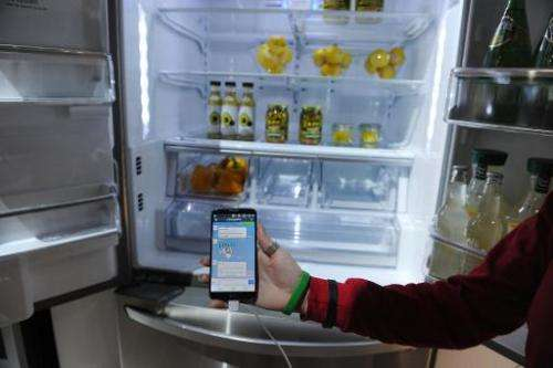 A LG representative shows a smartphone with Home Chat in front of a LG smart refrigerator at the 2014 International CES, January