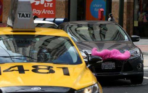 A Lyft car drives next to a taxi on June 12, 2014 in San Francisco, California