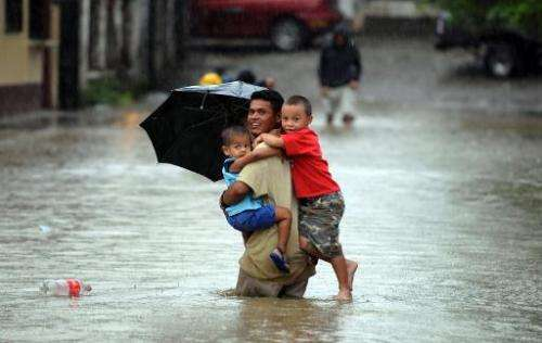 A man carries three children in a street flooded by the overflowing of Honduras' largest river, the Ulua, in El Progreso municip