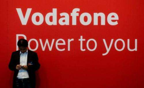 A man checks his mobile phone at the Vodafone stand at the IFA (Internationale Funkausstellung) electronics trade fair in Berlin