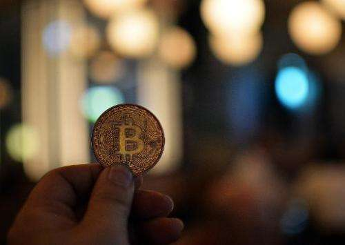 A man holds a bitcoin medal as members of bitcoin trading club hold a meeting in Tokyo on February 27, 2014