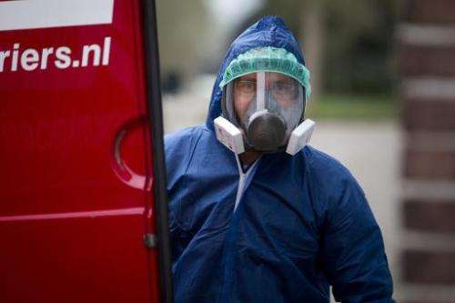 A man in protective gear looks on as Dutch authorities arrive at a poultry farm in Ter Aar, the Netherlands, on November 20, 201