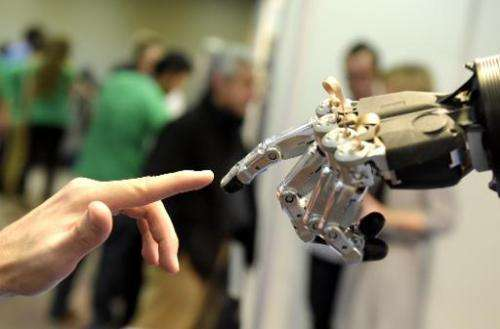 A man moves his finger toward an SVH automated hand made by Schunk during the 2014 IEEE-RAS International Conference on Humanoid
