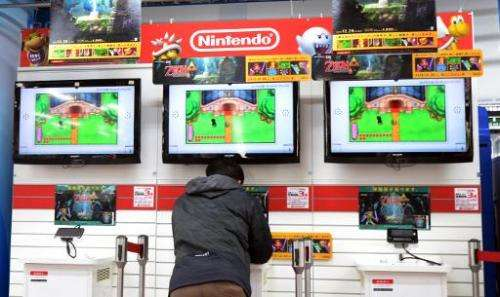 A man plays on a Nintendo portable video game console at an electronics shop in Tokyo on January 17, 2014