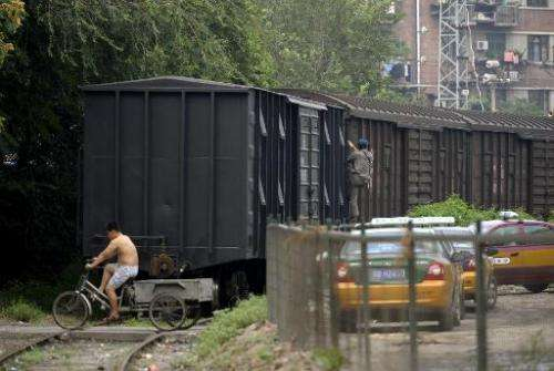 A man rides a tricycle over the rails next to a cargo train in Beijing on August 7, 2009