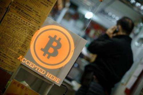 A man talks on a mobile phone in a shop displaying a bitcoin sign in Hong Kong on February 28, 2014