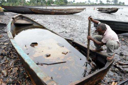 A man tries to separate crude oil from water in a boat at the Bodo waterways polluted by oil spills attributed to Shell equipmen