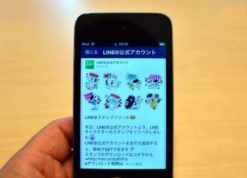 """A man uses a smartphone-based social networking service (SNS) """"LINE"""" in Tokyo on August 3, 2014"""