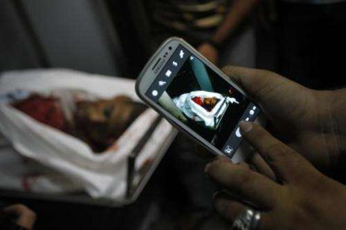 A man uses his mobile phone to take a picture of the body of a Palestinian militant killed in an Israeli strike, at the Nasir Ho