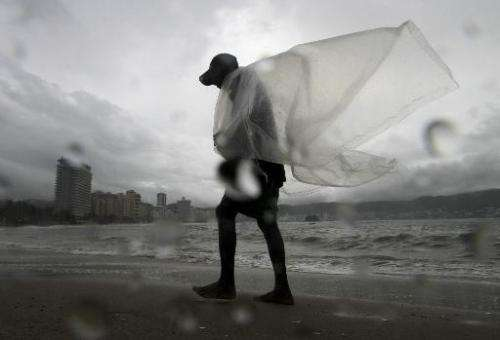 A man walks on the beach during a tropical storm in Acapulco, Guerrero State, Mexico on September 17, 2014