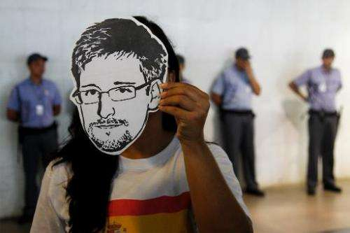 "A member of the Avaaz online community organization wears a ""Snowden"" mask in Brasilia, on February 13, 2014"