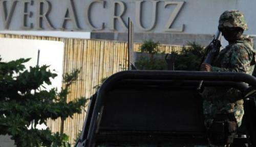 A Mexican Marine stands guard over a truck at a check point in the city port of Veracruz, Mexico on September 9, 2012