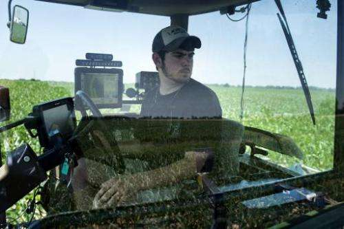 Andrew Isaacson watches from a tractor in a corn field as screens show where he has fertilized at the Little Bohemia Creek farm