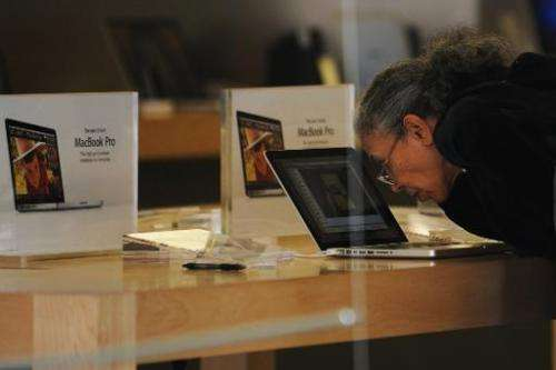 An elderly woman checks out a laptop computer at an apple store in Bethesda, Maryland, on May 12, 2010