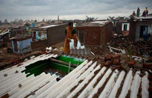 An Indian fisherman's wife prepares to fix a roof damaged in cyclone Phailin at Nalianuagaon in Ganjam district of Odisha in Oct