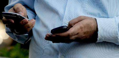An Indian officegoer checks a text message on his mobile phone in Mumbai on September 27, 2011