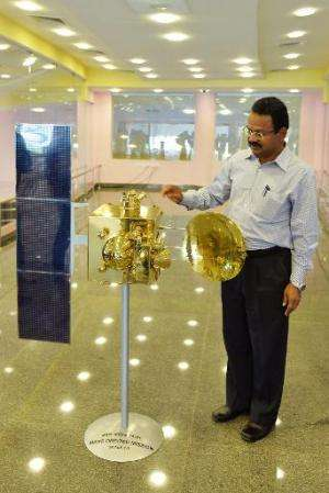 An Indian Space Research Organisation official uses a scale model of the Mars Orbiter Mission spacecraft to explain how parts of