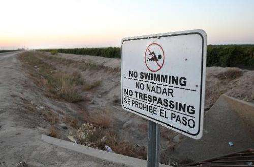 A no swimming sign is posted next to a dry irrigation canal on August 22, 2014 in Madera, California as a severe drought continu