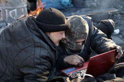 Anti-government protesters read the latest news via the internet on a laptop at a barricade in Kiev on February 5, 2014