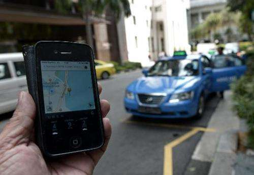 A person in Singapore uses an iPhone to order a taxi
