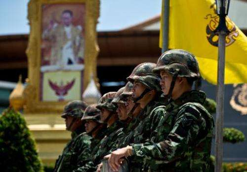 A portrait of Thai King Bhumibol Adulyadej is seen as Thai soldiers stand guard outside the Army club in Bangkok on May 21, 2014