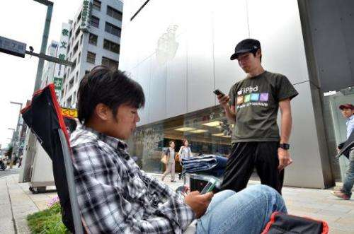 Apple gadget fans queue outside of an Apple store for the iPhone 6's release in Tokyo, on September 10, 2014