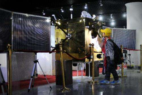 A pupil looks at the Chang'e-1 satellite at an astronomy museum in Beijing on December 11, 2013