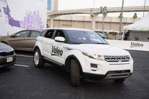 A Range Rover Evoque equipped with Valeo self-parking technology backs into a parking spot during a driverless car demo at the 2