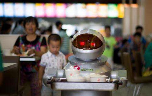 A robot carries food to customers in a restaurant in Kunshan, China on August 13, 2014
