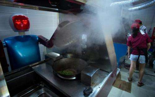 A robot cooks vegetables in a kitchen of a restaurant in Kunshan on August 13, 2014