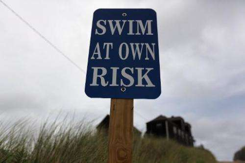 """A sign reads, """"Swim at Own Risk"""" at Ballston Beach on Cape Cod on August 12, 2012 in Truro, Massachusetts"""