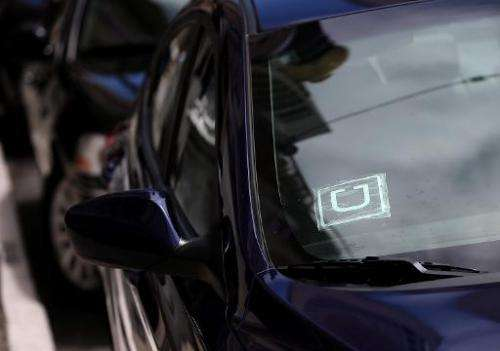 A sticker with the Uber logo is displayed in the window of a car on June 12, 2014 in San Francisco
