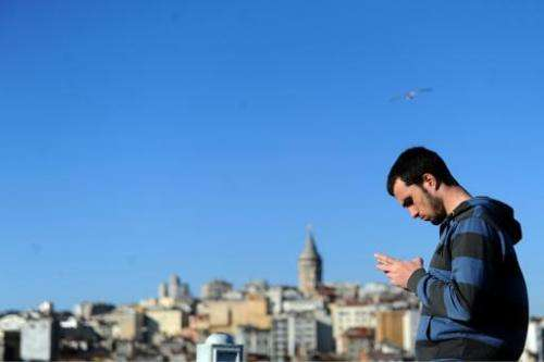 A Turkish man uses his smartphone, in the Eminonu district of Istanbul, on March 21, 2014