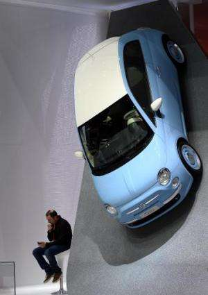 A visitor sits next to a Fiat 500 displayed at the Italian carmaker's booth during the press day of the Geneva Motor Show in Gen