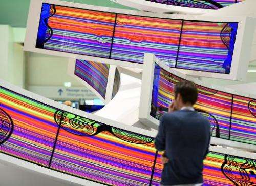 A visitor stands in front of curved television sets displayed at the Samsung booth at the consumer electronics trade fair in Ber