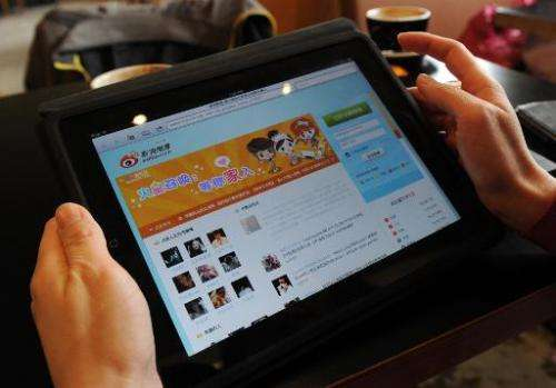 A woman views the Chinese social media website Weibo at a cafe in Beijing on April 2, 2012