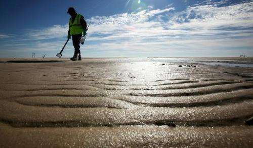 A worker cleans tarballs from the BP oil spill on Waveland beach December 6, 2010 in Waveland, Mississippi