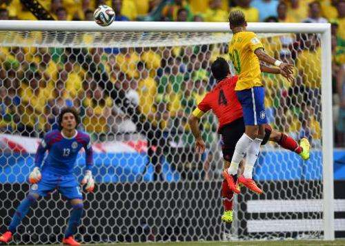 Brazil's forward Neymar (R) and Mexico's defender Rafael Marquez (C) jump for the ball in front of Mexico's goalkeeper Guillermo