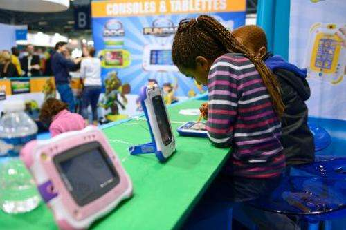 "Children play with digital tablets on October 19, 2013, during the ""Kidexpo"" show at the Porte de Versailes exhibition"