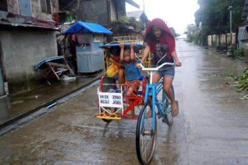 Children ride on a pedicab as it rains in Dolores town, eastern Samar, central Philippines on December 6, 2014